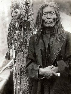 Siberian shaman, 1800s. He's standing next to an ongon, or 'spirit house' covered with ornaments.
