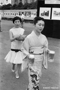 Two Japanese women at an outdoor art show or festival. 1958?