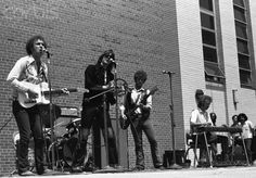 The Flying Burrito Brothers (Bernie Leadon, Gram Parsons, Chris Hillman, and Sneaky Pete Kleinow) performing at Queens College in New York, May 21, 1970.