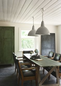 scandinavian home: a cool vintage inspired guest house. dining room. rustic wood board table (green?). green stained weathered wardrobe. white pendant lamps. white plank ceiling. rustic wood floor.