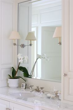 Large framed mirror with sconces mounted on glass