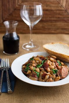 White bean stew with bacon, sausage, and spinach - a hearty white bean stew flavored with smokey bacon. Chicken sausage and baby spinach keep it healthy.