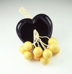A beautiful vintage black and cream Bakelite and celluloid heart and cherry dangle brooch.