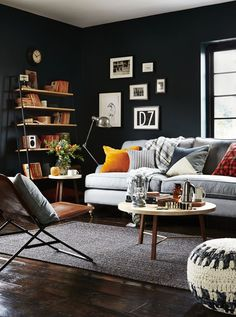 Offset a dark wall colour with sumptuous textures. Combine a traditional wool upholstered sofa with a sleek chair in burnished leather and pared-back framed pictures.