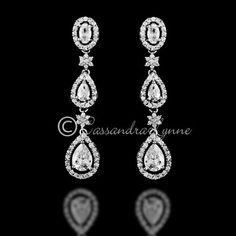 These dangle CZ earrings are designed with pave teardrop jewels and tiny flowers. Smaller but sparkly! They are about 1 and 5/8inches long, post backs.