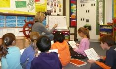 Teacher Beth Newingham sits in front of her class demonstrating something on a s