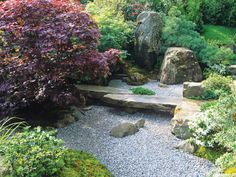 The careful landscaping in a Japanese garden invites one to stop and reflect. A large flat stone serves as a bench above a gravel groundcover.