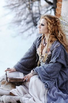 A medieval style of costume in the snow, a maiden reading.  I love the colors here so much.
