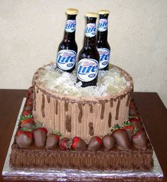 Three Miller Lite bottles on the top tier of the round cake and chocolate-covered strawberries on the bottom square cake