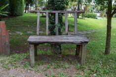 An armless wooden garden bench resting under a tree.