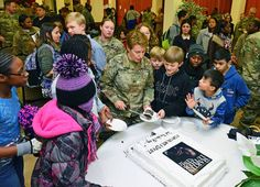 Colonel Christine A. Beeler, commander of the U.S. Army 414th Contracting Support Brigade, serves cake to children, during Martin Luther King, Jr. Day observance, at Vicenza Military Community's 2017 Observance Ceremony at Caserma Ederle, Vicenza, Italy.