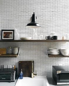 Kitchen vignette with an industrial light fixture, pencil subway tiles and raw wood open shelving.