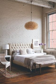 tall ceiling, neutral palette, upholstered headboard - brick wall