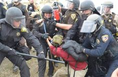This woman is holding a Native America prayer staff and protesting on her own lands.  The angry mob is the Morton County Sheriff's department, dispatched in full riot gear to ensure protection of the pipeline crew as they illegally build on Native sovereign land. When they filed their report, they said she was wielding a gun. America.  2016