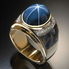 RANDY POLK DESIGNS: MEN'S RINGS. A 20 ct high - dome Burmese Star Sapphire Petersite inlay and 16 pave Diamonds.