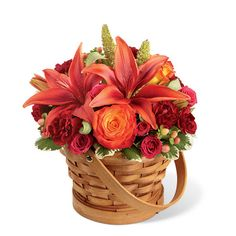 Thanksgiving flower arrangement: Dark orange Asiatic lilies, bi-colored orange roses, burgundy miniature carnations, fuchsia spray roses, peach hypericum berries and millet grass in a wood basket