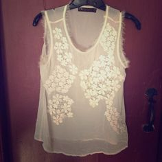 See through cream colored camisole with flowers. See through cream colored camisole with flowers embroidered on front.  Frayed edged around neck and arms. The Limited Tops Camisoles