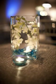 I love submerged flowers. Teal/Aqua marbles with white flowers as understated and DIY centerpieces