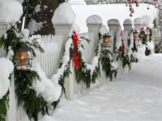 White picket fence with green garland, red bows & lanterns.  LOVE this idea!!!  Want to get rid of my wreaths & do this instead!!!!