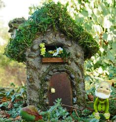A little gnome poses in front our sunshine fairy house in our miniature fairy garden.
