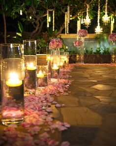 candlelit ceremony. pink roses petals lining aisle. at Disney Aulani Resort. flowers by Sweet Pea & Petunia.