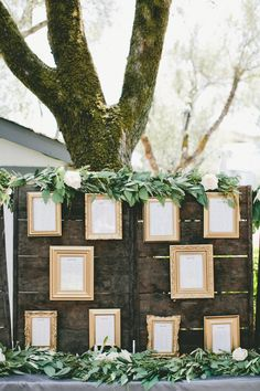 Each gold frame on this rustic seating chart features a different table and the names of guests who will sit at each. The effect, when combined with a little bit of greenery, is stunning.