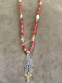 Collar Largo perla de vidrio pintado en tonos rojos y dije Mano de Fatima, adornado con cristales en tonos champagne