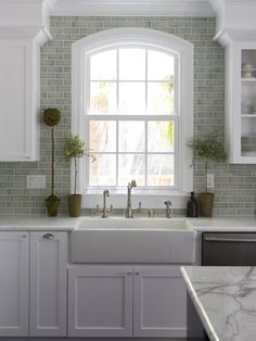 A ceramic farmhouse sink with a brushed-nickel faucet anchors this serene transitional kitchen. Countertop topiaries and a green subway-tile backsplash create an earthy backdrop for crisp white cabinetry and an arched window.
