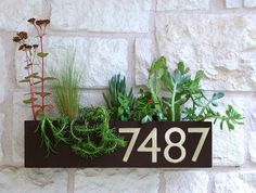 Welcome Home. This modern address plaque and trough wall planter adds flair and style to the facade of your home with aluminum address numbers. Looks