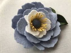 Lovely felt flower brooch, handmade from a merino wool blend felt in cornflower blues and crisp white with rich butter accents. I use a 100% wool ball to create the center. The highly detailed floral stamens are created by using wool felt in a 3-step process. This felt flower measures
