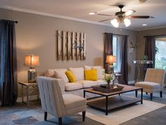 "Just off the kitchen and dining area, the new sitting room has modern slate floors and simple, gray linen window treatments. The home's original wainscoting was removed, modernizing the space, and the walls were painted a warm beige. To add contrast to the room, Joanna brought in bright yellow pillows and shiny, metallic lamps and tables, while a white picket gate with the work ""family"" attached to it hangs above the cozy, white sofa, softening the space.  (After 14)  AFter"
