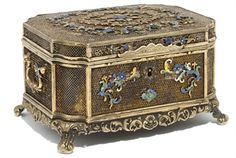 A chinese export silver filigree and enamelled box, 19th century.  Of rectangular form with canted corners, with twin loose c-scroll handles, the fine filigree placed upon a silver gilt body with applied foliate enamel decoration to the sides of the body, the interior of the cover with a reverse glass painted mirror depicting long tailed birds perched on rockwork and a foliate border, the whole raised on four supports