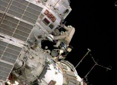 Russian space station crew member Oleg Artemiev floats outside the International Space Station during a space walk by two Russians to install a new antenna and move a cargo boom.