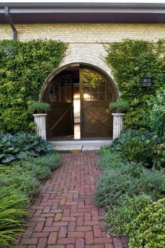 A paved brick walkway leads to 10-foot-tall front doors that mark the entrance in this artillery stable-turned-home.  - Traditional Home ® / Photo: Werner Straube / Design: Judith Nadler Ellerman
