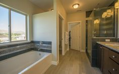 Adair Homes   Plan 2734 - This stunning master bathroom features a custom shower, tile floors and tub surround, custom cabinets and so much more. Your possibilities are endless when building your own home.