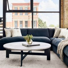 "There is not a whole lot you can say about the Round Coffee Table with Iron that the name doesn't already say. Cool neutrals combine in a thick charcoal finished mango wood top and slim, flat stock gunmetal base. Tone on tone finishes and x-shaped stretchers add movement. 48""W x 48""D x 15.5""H"