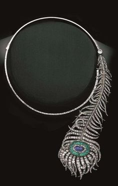 An important peacock feather necklace by Boucheron with Royal Russian provenance. Set with a sapphire, emeralds and diamonds, the feather is detachable and may be worn as a brooch or hair ornament. Paris, 1883.
