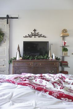 Television decorated for Christmas, with greenery and cone-shaped Christmas trees.