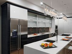 This ultra modern kitchen boasts high-end finishes like a waterfall countertop island, black subway tile backsplash, drop chandelier and horizontal glass front cabinets for a sleek, refined space.
