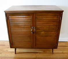 """Mid Century Modern Slatted Server Cabinet with Brass Handles - This is a mid century modern slatted server cabinet made of solid wood.  It has solid wood shelves, tapered legs, and beautiful brass handles.  Great to use as a kitchen or serving cabinet, console table with storage, the list goes on… Dimensions: 29""""W x 16.5""""D x 29.5""""H. *SOLD*"""