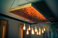 Custom edison bulb chandelier.  Made with bronzed copper ceiling tiles, and poplar wood trim.