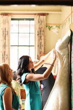 I love this photo of friends preparing the dress