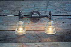 This is an industrial styled wall sconce made from recycled glass insulators and black cast iron pipe. The lamp utilizes two antique glass insulator