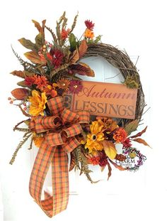 Autumn Blessings Wreath with fall silk flowers, faux feathers, sign and large bow. Warm up your entry way this fall with a new front door wreath.  If you are busy like me and don't have time to decorate or make your own wreaths, then let me help you. To get that fabulous looking fall door, just hang this wreath and purchase pre-planted fall mums from your local hardware store to sit on either side of the door; instant warm and inviting entryway. Design by www.southerncharmwreaths.com