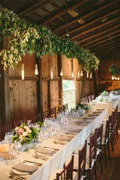 Hanging lights and long tables gussy up a barn reception / http://www.deerpearlflowers.com/20-stunning-rustic-edison-bulbs-wedding-decor-ideas/