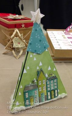 The box is a three-sided triangle, each with three houses on the outside, it then opens up to reveal yet more houses and a Christmas tree.