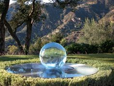 A hidden pump sends gentle streams of water down the sides of the 2-foot-tall Aqualens acrylic sphere, which then pools in a 5-foot-wide steel dish. The sphere can also be illuminated. (allisonarmour.us)