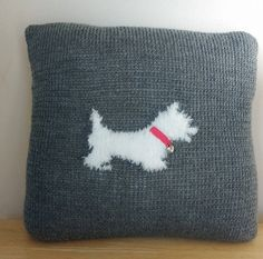 Hand knitted cushion with a fluffly velour style wool Scotty dog design knitted into the middle. The collar of the dog is made using ribbon and a metal heart has been added as a tag detail. This cushion measures approximately 37cm square. Colours of the background and the ribbon collar can be changed on request.  This item is custom made to order so please allow 3 weeks for making and then upto a week for delivery. Orders will be posted using myHermes and a tracking number will be supplied…