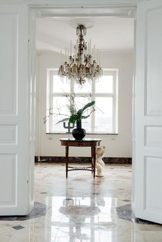 Glamorous foyer with crystal chandelier, black vase, and bust
