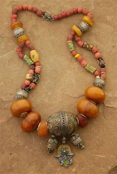 """The Hand of Fatima and two barrels dangle from the large Berber """"egg"""" that is the focal point of this piece. Large copal amber beads, Venetian trade beads, smaller Berber and amber beads and coral-colored glass complete the strand. Ethnic Jewelry, Moroccan Jewelry, African Jewelry, Boho Jewelry, Jewelry Art, Beaded Jewelry, Jewelery, Silver Jewelry, Jewelry Necklaces"""